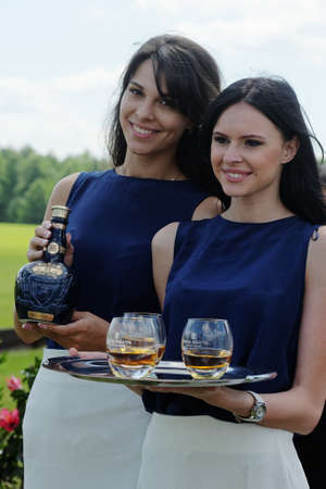 Tseleevo, Moscow region, Russia - July 26, 2014: Girls offer the whiskey Royal Salute to the guests of the British Polo Day. It was the second British Polo Day in Russia Editorial