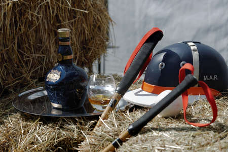 Tseleevo, Moscow region, Russia - July 26, 2014: Equestrian helmet, polo mallets, and a bottle of Scotch whiskey on the bales of hay during the British Polo Day. It was the second British Polo Day in Russia Editorial