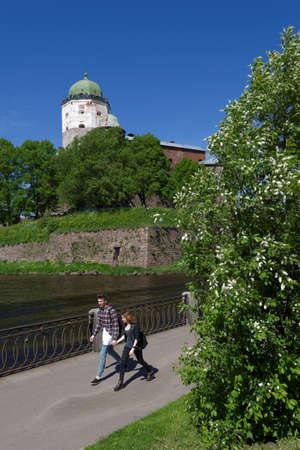 leningrad: Vyborg, Leningrad oblast, Russia - June 6, 2015: People on the embankment against the tower of St. Olav of Vyborg Castle. The castle was founded in 1293