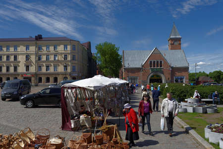 Vyborg, Leningrad oblast, Russia - June 06, 2015: People at the market square. The market building was erected in 1904-1904 by design of Karl Segerstad
