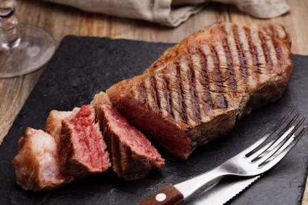 スレートのまな板の上の焼き霜降り牛ステーキ