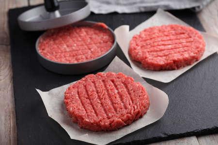 肉を押すと牛ひき肉からハンバーガーを調理 写真素材