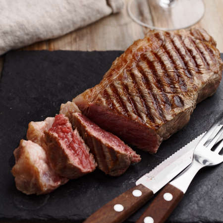 Grilled marbled beef steak on a slate cutting board Stock Photo