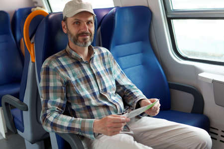 Mature man holding tickets in a commuter train photo