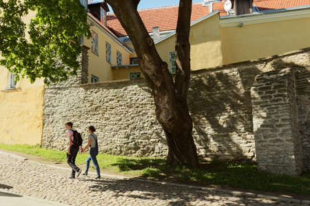 Tallinn, Estonia - June 10, 2017: Young people walking on the street of Old city. The Old Town is one of the best preserved medieval cities in Europe and is listed as a UNESCO World Heritage Site