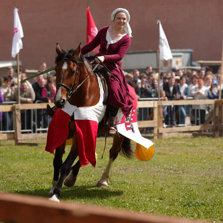 reenactment: St. Petersburg, Russia - July 9, 2017: Women in medieval clothes with sword on a horse during the festival Battle On Neva at St. Peter and Paul fortress. The main event this year is jousting tournament