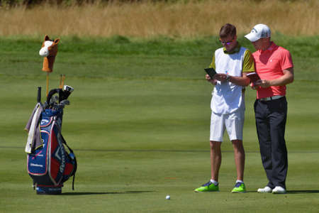 Tseleevo, Moscow region, Russia - July 26, 2014: David Horsey of England (rightr) with his caddy on the course in the Tseleevo Golf & Polo Club during the 3rd round of M2M Russian Open. This international golf tournament is the stage of the European Tour