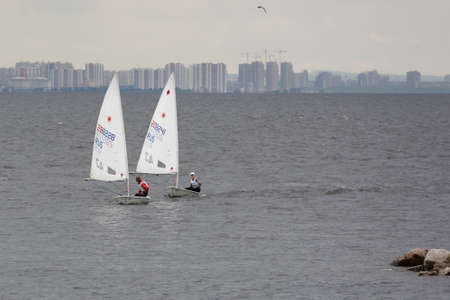 St. Petersburg, Russia - July 5, 2017: Training in sailing on Laser 4.7 dinghy in the Gulf of Finland near the yacht club of St. Petersburg. Sponsored by Gazprom, yacht club organises sailing classes for all ages and holds sports regattas