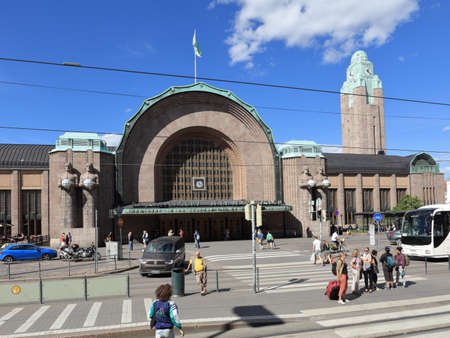 Helsinki, Finland - July 15, 2017: People at the central railway station in a summer day. The station building was designed by Eliel Saarinen and inaugurated in 1919