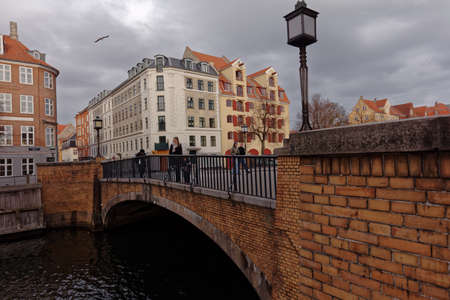 Copenhagen, Denmark - November 07, 2016: People walking on Snorrebro bridge across Chrisianshavn canal. The canal is noted for its bustling sailing community with numerous house- and sailboats Editorial