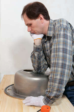 Worker in doubts during the kitchen sink installation