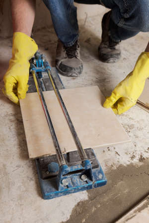 Tiler cutting ceramic tiles during floor installation Stock Photo