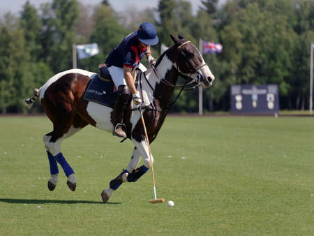 Tseleevo, Moscow region, Russia - July 26, 2014: Unidentified player of British schools with mallet in the match against Moscow Polo Club during the British Polo Day. Bacon become the best player of the match
