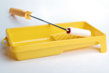 Paint roller, tray, and a can of paint on white background