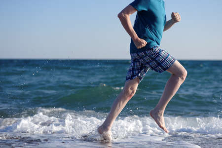 Barefoot mature man during jogging on a beach