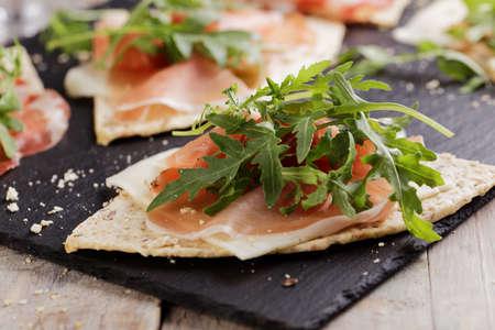 Sandwiches met Prosciutto, plakjes kaas en rucola op partjes van piadina