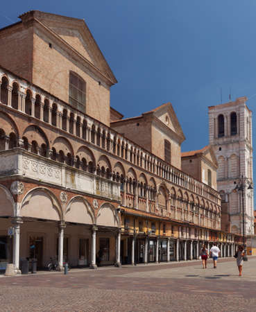 Ferrara, Italy - June 17, 2017: People on the Piazza Trento - Trieste in a summer day. The bell tower of St. George Cathedral built in XVI century by design of Leon Battista Alberti is visible on the right