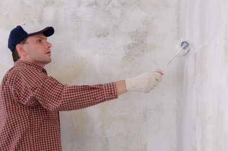Man painting a wall using paint roller