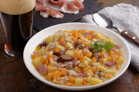 Traditional Irish dish Dublin coddle with sausages and beer on a table