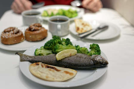Baked trout with steamed broccoli and lemon Stock Photo