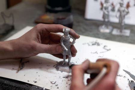 St. Petersburg, Russia - February 21, 2017: Worker solders the base during the production of tin soldiers in the Niena studio. Created in 1992, the enterprise supplies souvenirs around the world including Australia