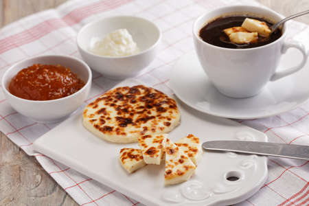 Swedish breakfast with mini farmer cheeses, cloudberry jam, whipped cream, and a cup of coffee Stock Photo