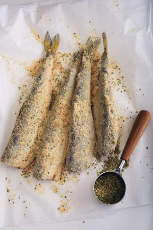Breaded smelt fish with spices before roasting