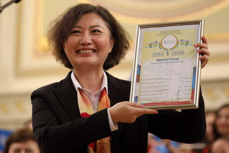 Saint-Petersburg, Russia - February 25, 2018: Zhang Jinjin, artistic director of Xiaman Media Group Students Choir Happy Childhood, China with the diploma of V Children and Youth World Choral Championship