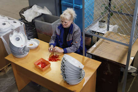 St. Petersburg, Russia - March 15, 2018: Female worker at work in the plastics recycling plant named after newspaper Komsomolskaya Pravda. The plant produces plastic products since 1931, and now it involved in plastics recycling Redakční
