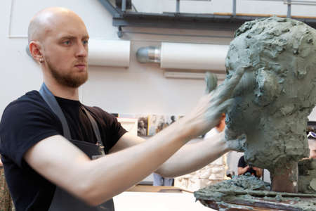 St. Petersburg, Russia - July 15, 2018: Sculptor Vitaly Datchenko participates in artistic battle during the opening of festival Laboratory Of Sculpture in the museum workshop of sculptor Mikhail Anikushin. The festival includes master classes and battles