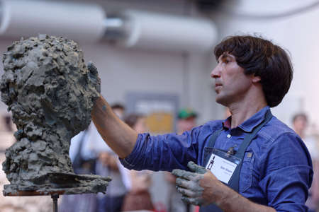 St. Petersburg, Russia - July 15, 2018: Sculptor Oleg Shorov participates in artistic battle during the opening of festival Laboratory Of Sculpture in the museum workshop of sculptor Mikhail Anikushin. The festival includes master classes and battles