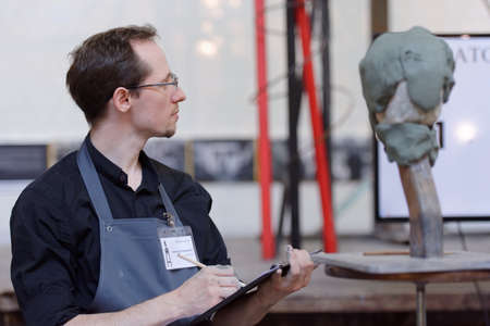 St. Petersburg, Russia - July 15, 2018: Sculptor Alexander Spiridonov participates in artistic battle during the opening of festival Laboratory Of Sculpture in the museum workshop of sculptor Mikhail Anikushin. The festival includes master classes and bat Редакционное