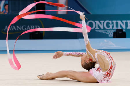 Kiev, Ukraine - August 29, 2013: Unidentified female gymnast performs with ribbon during 32nd Rhythmic Gymnastics World Championships. The event is held in Palace of Sport