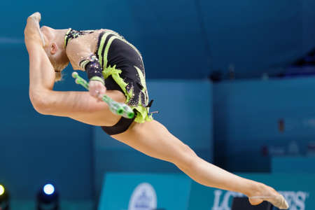 Kiev, Ukraine - August 29, 2013: Unidentified female gymnast performs with clubs during 32nd Rhythmic Gymnastics World Championships. The event is held in Palace of Sport Editorial
