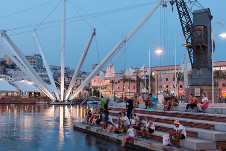 Genoa, Italy - August 5, 2018: People resting at sea in the old port, Porto Antico in a summer evening. The panoramic lift, Bigo, which offers a full view of the harbor and city, is visible on the back left side