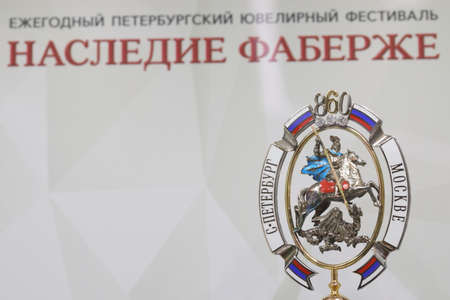 St. Petersburg, Russia - February 1, 2019: Jewelry produced by the factory Russkiye Samotsvety and dedicated to 860th anniversary of Moscow city against banner of jewelry festival Faberge Heritage. The festival includes jewelry exhibitions, master classes
