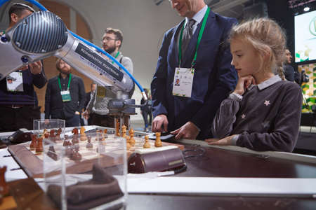 St. Petersburg, Russia - December 27, 2018: Robot playing chess with people in Exhibition Hall Manege during World Rapid and Blitz Chess Championship 2018. The robot simultaneously plays on 3 chess boards