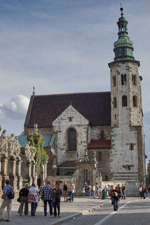 Krakow, Poland - August 27, 2006: People on Grodzka street against the Church of St. Andrew in the old town. This Romanesque church built in 1079-1098 is a rare surviving example of the European fortress church used for defensive purposes