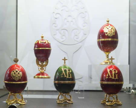 St. Petersburg, Russia - February 1, 2019: Faberge eggs with Russian coat of arms and Easter symbols produced by the factory Russkiye Samotsvety in the opening day of jewelry festival Faberge Heritage. The festival includes jewelry exhibitions, master cla Editorial
