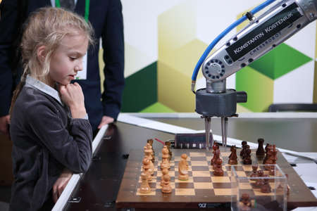 St. Petersburg, Russia - December 27, 2018: Robot playing chess with a girl in Exhibition Hall Manege during World Rapid and Blitz Chess Championship 2018. The robot simultaneously plays on 3 chess boards Editorial