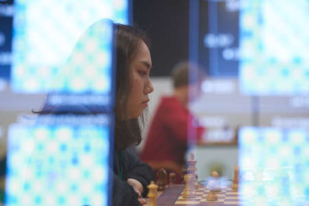 St. Petersburg, Russia - December 30, 2018: Grandmaster Lei Tingjie, China competes in King Salman World Blitz Chess Championship 2018. Eventually she took 3rd place. Multi-exposure Editorial