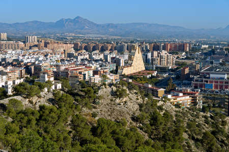 Alicante, Spain - January 8, 2013: Cityscape viewed from the Mount Benacantil. Pyramid-shaped building in center is Edificio Montreal, built in 1980s and referred as one of ugliest buildings in Spain Editorial