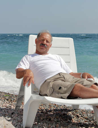 Senior man resting in the chaise lounge on a pebble beach against a sea