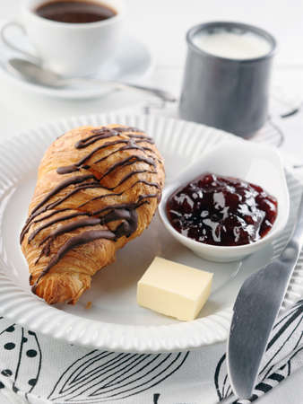 French breakfast with croissant, butter, yogurt, strawberry jam, and black coffee