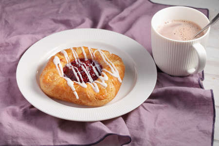 Danish pastry with jam and a cup of hot chocolate
