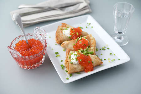 Blinis with red caviar and sour cream decorated with green onion