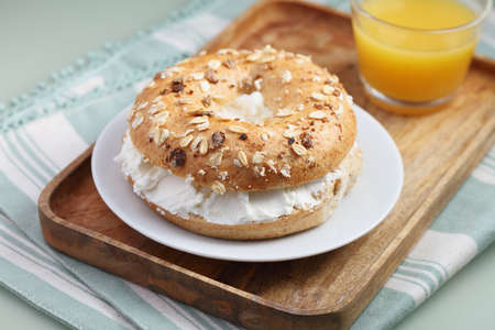 Bagel sandwich with soft cheese and a cup of orange juice on a wooden tray