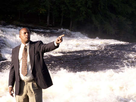business man in a suit standing in front of a rushing river with finger pointing Stock Photo - 255792