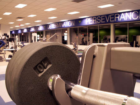 empty fitness center with freeweights in focus in foreground