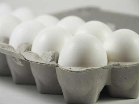 carton of a dozen eggs with focus on front corner of carton photo